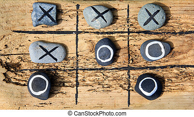 Tic tac toe game made from drift wood and rocks for outdoor...