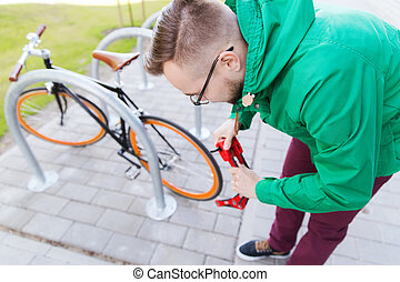 hipster man fastening fixed gear bike with lock - people,...