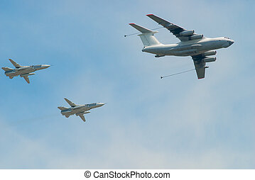 military aircraft with fuel and two fighters in the sky to refuel