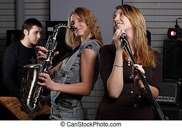 two young females sign the song and play on saxophone