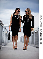 Two attractive hispanic businesswomen walking outdoor...