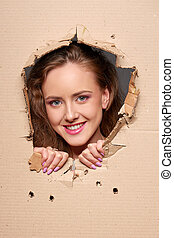Looking through paper hole - Beautiful smiling woman looking...