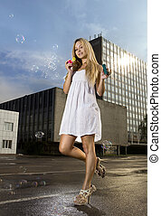 woman blowing soap bubbles on street - young blonde woman...