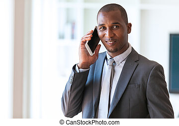 Portrait of a young African American business man using a...