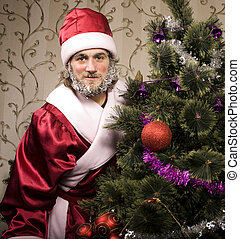 portrait of funny Santa Claus at home with christmass tree...
