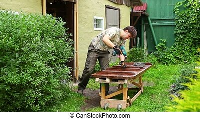 Young man carpenter - Young man carpenter making table