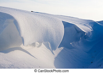 Snow dune in a ditch in winter