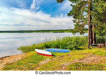 Two canoes on a lake bank