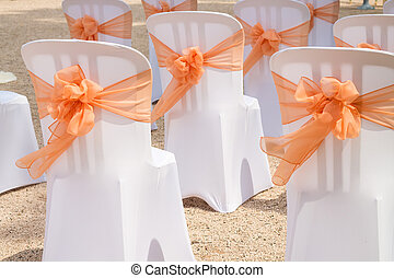 White Chairs with orange Bows. - Decorations at the Wedding...