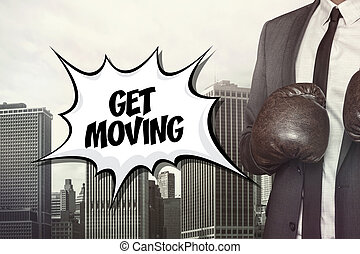 Get moving text with businessman wearing boxing gloves on...