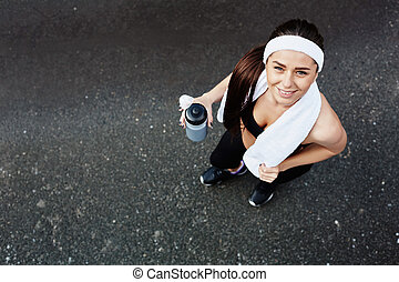 Happy sportswoman - Active girl with bottle of water looking...