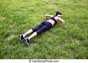 Doing pushups - Fit young woman practicing pushups outdoors