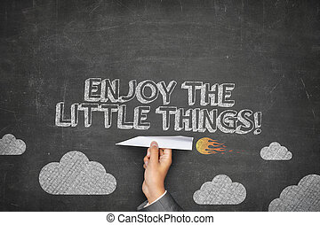 Enjoy the little things concept on black blackboard with...