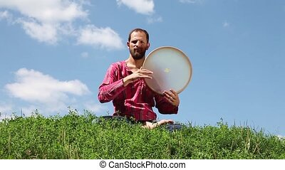 Young man playing the tambourine sitting on the green grass...