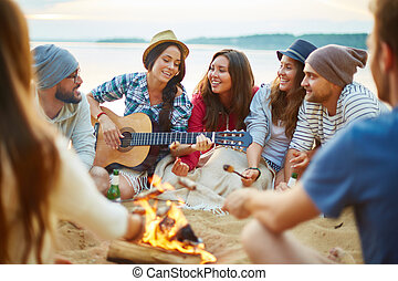 Campfire singing - Friendly girls and guys singing by guitar...