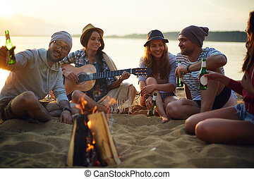 Evening in camp - Happy friends with drinks and guitar...