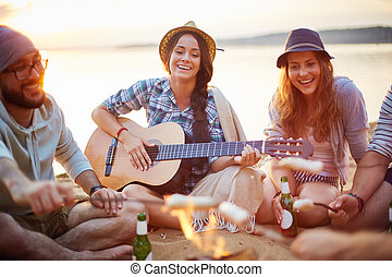 Happy girls - Friendly girls with guitar and drink singing...