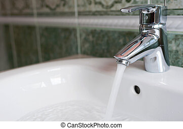 save water - water tap with flowing water in modern bathroom