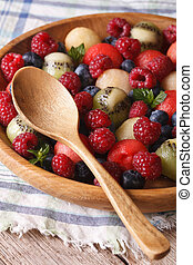 salad of fresh fruits and berries in a wooden bowl closeup. vertical