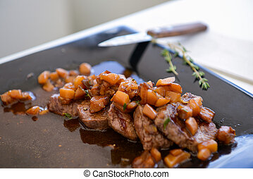dish of pork with sauce on black plate - delicious freshly...