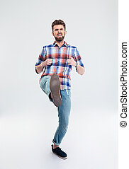 Full length portrait of angry man kicking