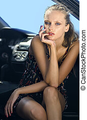 woman in the black car - fashionable young beautiful sad...