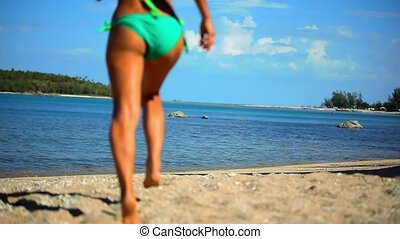 Sexy brunette is running into the sea, in a stylish green...