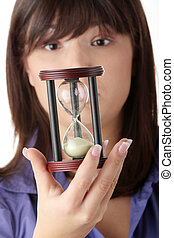Time - oung business woman with hourglass - time concept