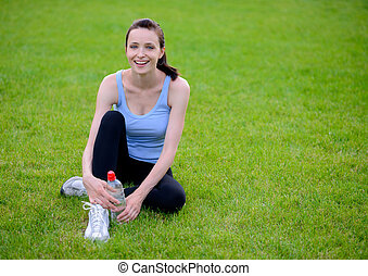 Beautiful Smiling Woman Relaxing on the Grass in the Park