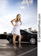 ambitious girl in a white dress near the black car