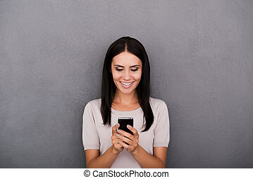Staying connected. Cheerful young woman holding smart phone and smiling while standing against grey background