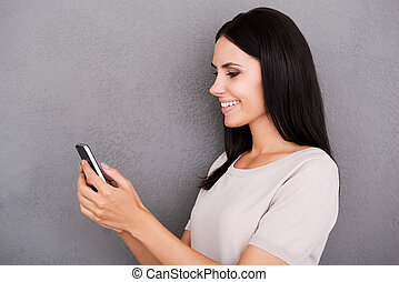Always in touch with her friends. Side view of cheerful young woman holding smart phone and smiling while standing against grey background