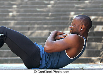 African american man sport training workout sit ups outside