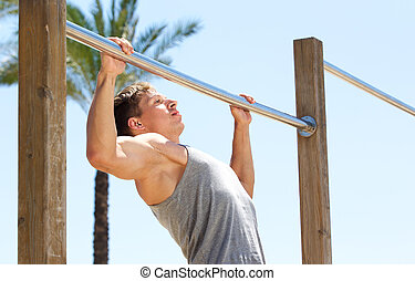 Young sports guy pull up exercise routine