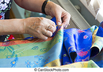 Hands sewing with needle and thread - female hands sewing...