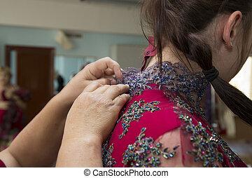 Fashion designer adjusting dress on model - close-up of...