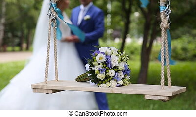 Bridal bouquet on a swing at wedding