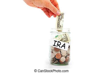 IRA savings - hand putting a dollar into a IRA coin jar,...