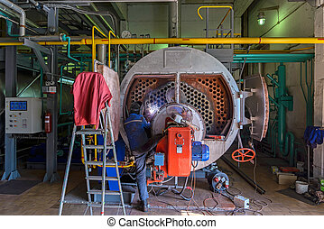 Repair of the boiler - Worker repairing the boiler with the...