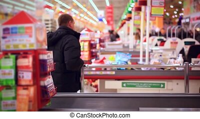 Man shopping at the supermarket. Blurred background with...