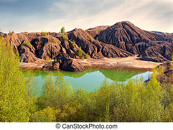Mountains of an unusual form are reflected in the lake with...