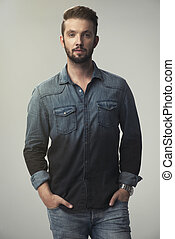 Young strong slim man in jeans shirt posing on gray background.