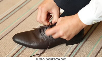Man puts on shoes Focus on the laces at wedding