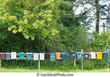 Mailboxes in a row at rural cabin site, Sweden summertime.