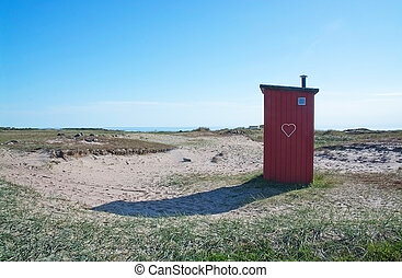 Small seaside toilet house in red wood with heart standing...