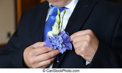 putting the boutonniere flower on a groom - hand putting the...