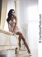 Beauty brunette woman in stylish room, wearing pink costume, ballet skirt and corset
