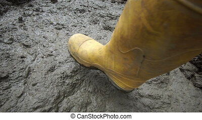 Rubber Boot Makes Muddy Step - High angle close up shot of...