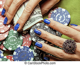 hands of young caucasian woman with blue manicure at casino...