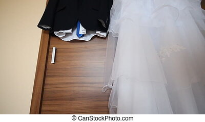 Bridegroom dress and bridal gown hanging in wardrobe
